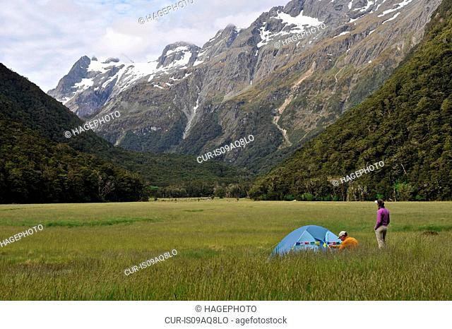 Couple camping in field with mountains, New Zealand