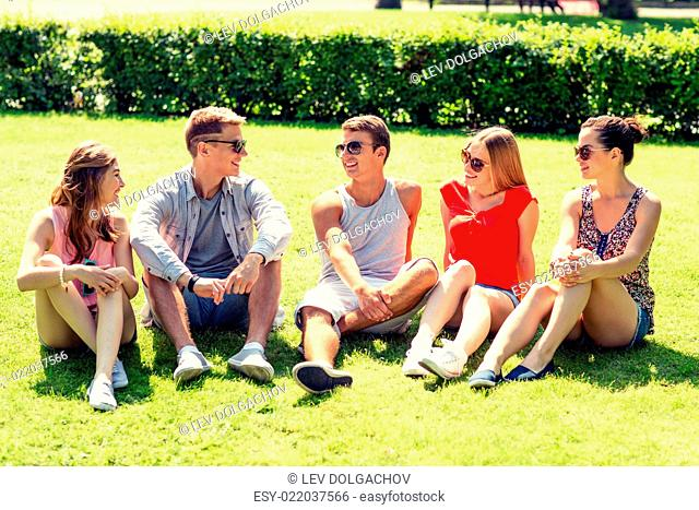 friendship, leisure, summer and people concept - group of smiling friends outdoors sitting on grass in park