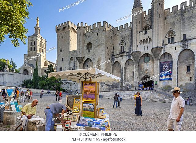 Artists selling paintings in front of the Palais des Papes / Palace of the Popes in the city Avignon, Vaucluse, Provence-Alpes-Côte d'Azur, France