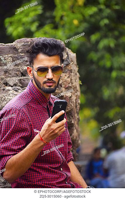 Young man with checked shirt looking at cell phone, Pune, Maharashtra, India