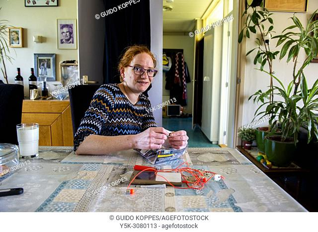 Roosendaal, Netherlands. Young adult redheaded woman smoking a cigarette using tabacco, while sitting at her domestic, dining room table