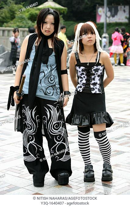 Teenage girls dressed in alternative street fashion relax in Harajuku, Tokyo, Japan