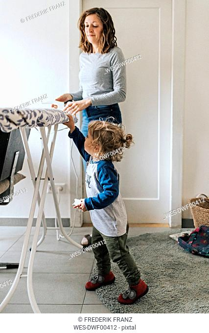 Mother and daughter at home with ironing board