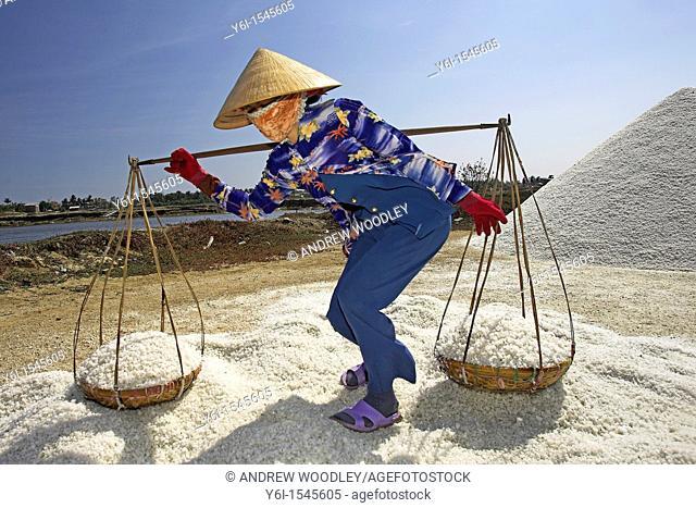 Woman in conical hat prepares to dump pannier baskets of salt on a new salt mound Vietnam