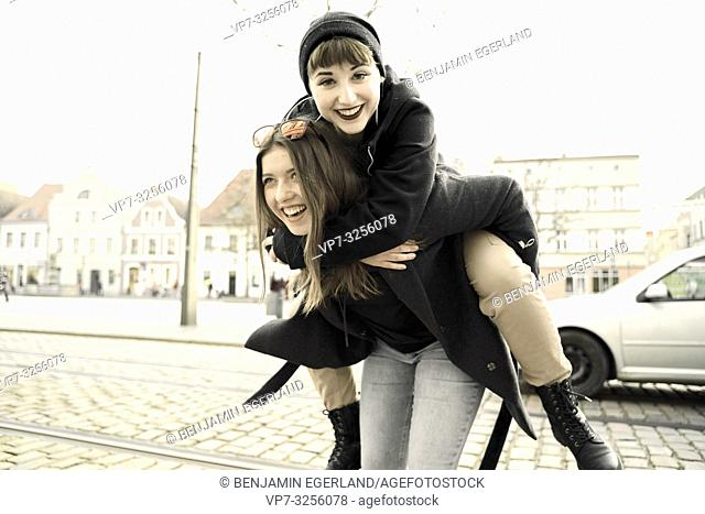 woman carrying best friend piggy back, happiness, at street in city Cottbus, Brandenburg, Germany