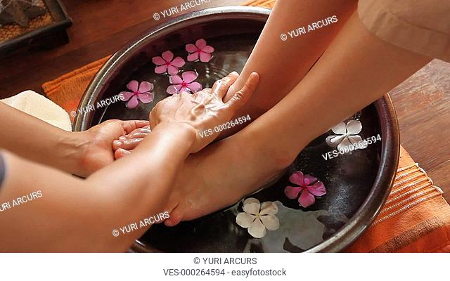 Cropped footage of a woman's feet being gently washed in a bowl of water and flowers