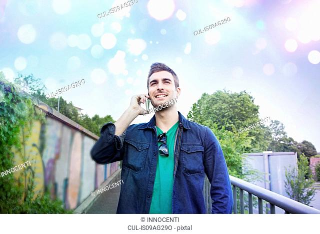 Young man talking on smartphone with glowing lights above