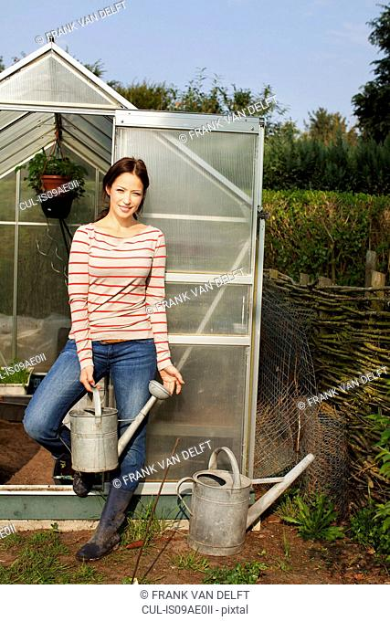 Young woman holding watering can by greenhouse