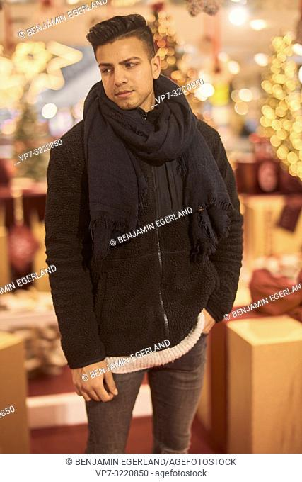 young man, Afghan ethnicity, in front of christmas decoration, in Munich, Germany