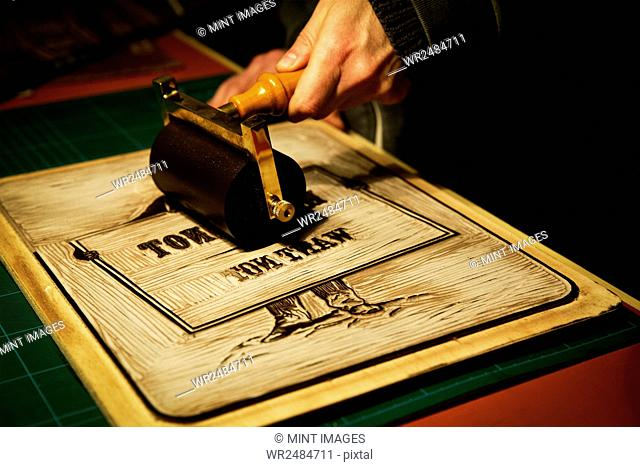 A sign maker rolling ink across the cut raised surface of linoleum preparing to print