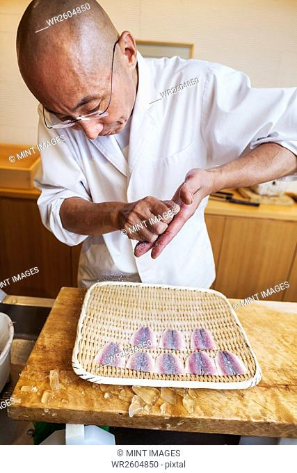 A chef working in a small commercial kitchen, an itamae or master chef making sushi, preparing fish