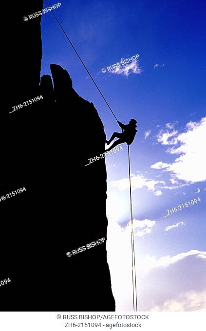 Silhouetted climber rappelling from the summit of Eichorn Pinnacle, Yosemite National Park, California USA
