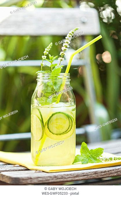 Glass of ice-cooled homemade lime cucumber lemonade with mint leaves