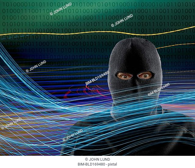 Caucasian burglar standing in technology light trails