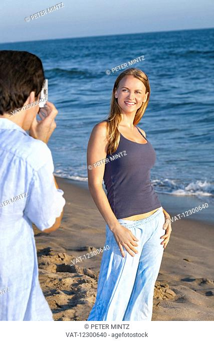 Man taking a photograph of a woman on the beach; Los Angeles, California, United States of America