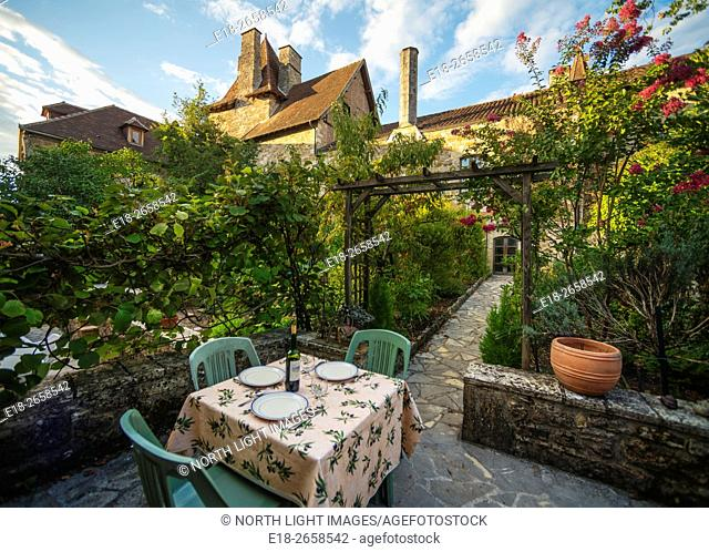 France, Midi-Pyrénées, Carrenac. Table and chairs set up in small private garden in the medieval village. Officially classified as one of the most beautiful...