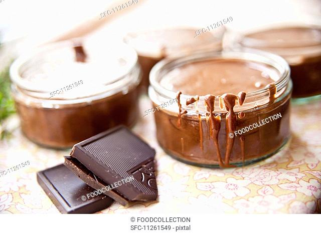Shallow screw-top jars filled with liquid chocolate
