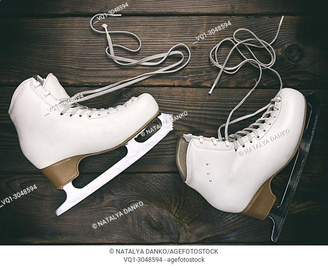 pair of old white female skates for figure skating with unbound laces lie on a brown wooden background, top view