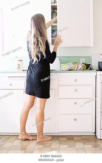 A woman with long blond hair standing barefoot in a kitchen, opening a cupboard