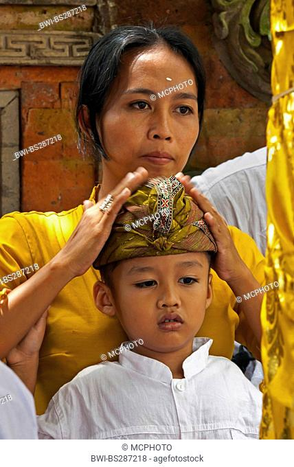 a young balinese boy and his mother is dressed traditionally during the Galungan Festival, Indonesia, Bali, Ubud