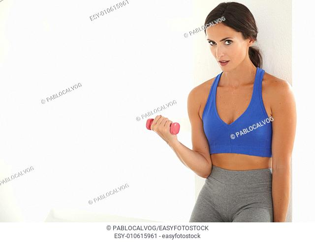 Sporty hispanic woman training with a dumbbell to lose weight while looking at you - copyspace