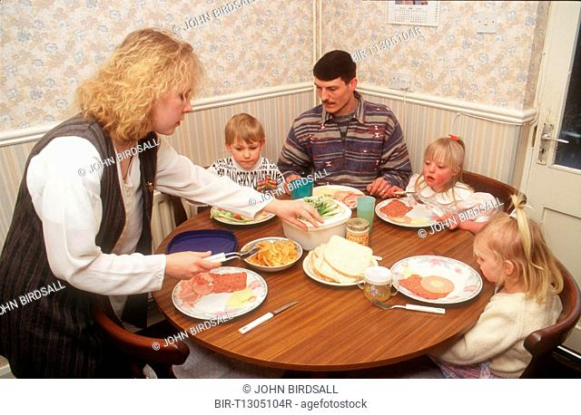 Family group with young girl with Downs Syndrome sitting at table eating meal