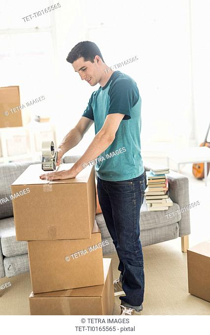 Man packing cardboard boxes at home