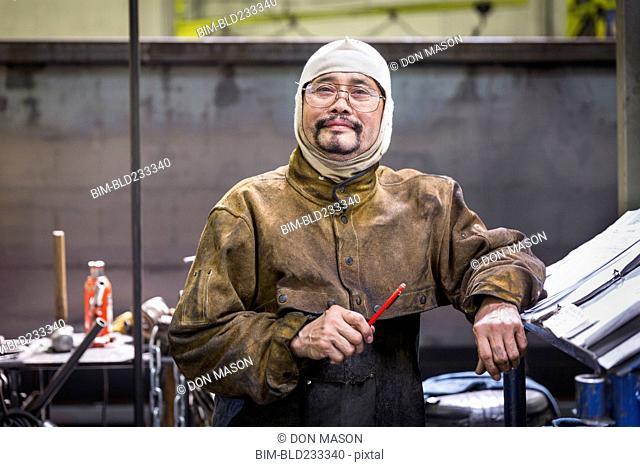 Smiling Asian worker wearing hood posing in factory