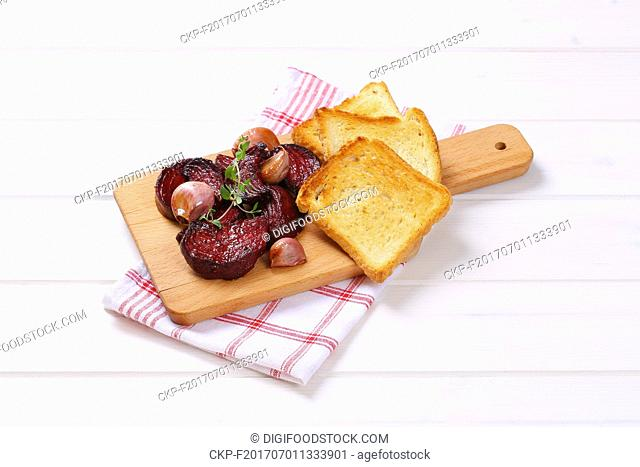 baked beetroot and garlic with toasted bread on wooden cutting board
