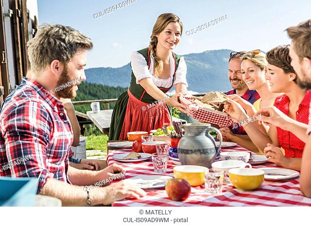 Group of friends at breakfast outside chalet, Tyrol, Austria
