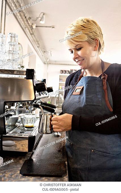 Barista heating up milk using coffee machine