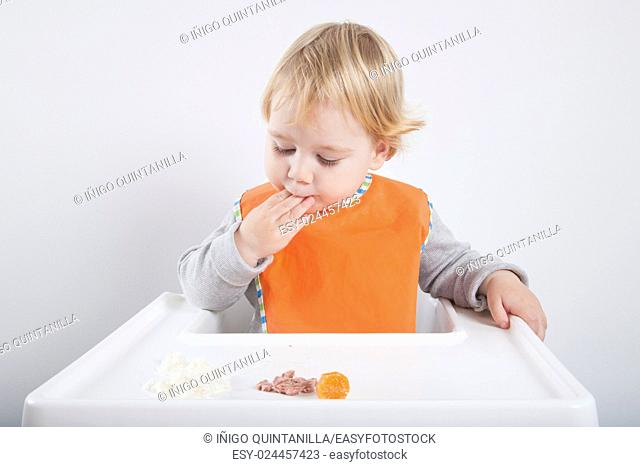 blonde caucasian baby seventeen month age orange bib grey sweater eating meal with her hand in white high-chair