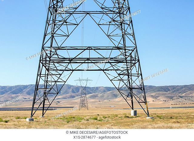 Base of a high voltage transmission tower with other towers in the distance