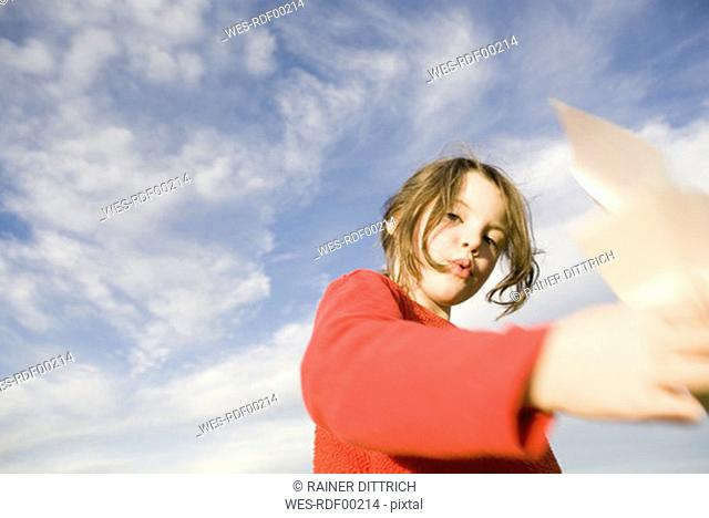 Girl 7-9 holding paper plane, blurred motion