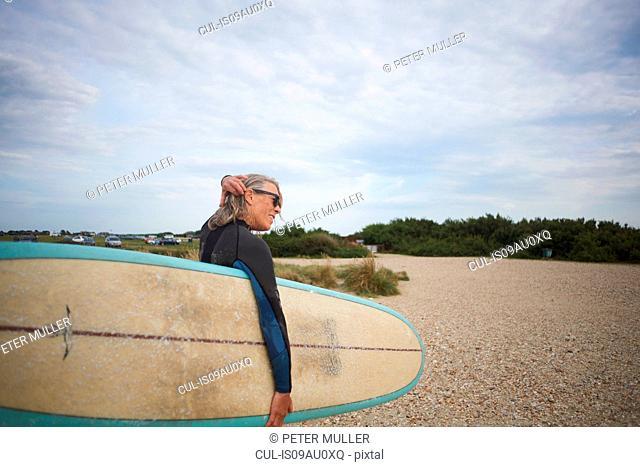 Senior woman walking along beach, carrying surfboard, rear view