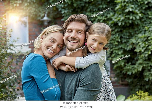 Portrait of happy family in garden of their home
