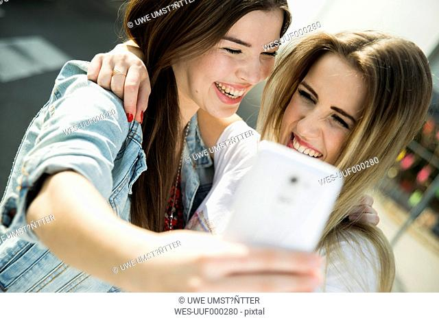 Two happy young women taking a selfie outdoors