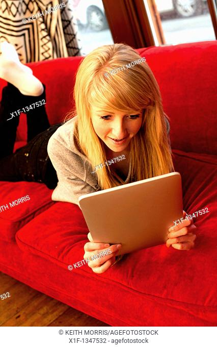 A fourteen year old teenage girl using a digital tablet to read Facebook and email at home, UK