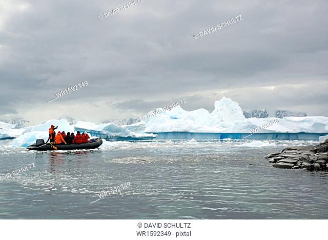 People in small inflatible zodiac rib boats passing icebergs and ice floes on the calm water around small islands of the Antarctic