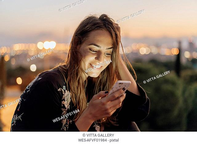 Spain, Barcelona, Montjuic, smiling young woman at dusk using cell phone