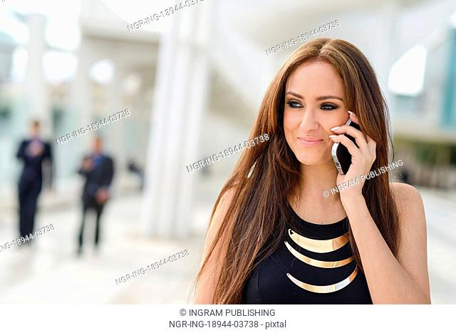 Portrait of beautiful young woman in urban background talking on phone and smiling
