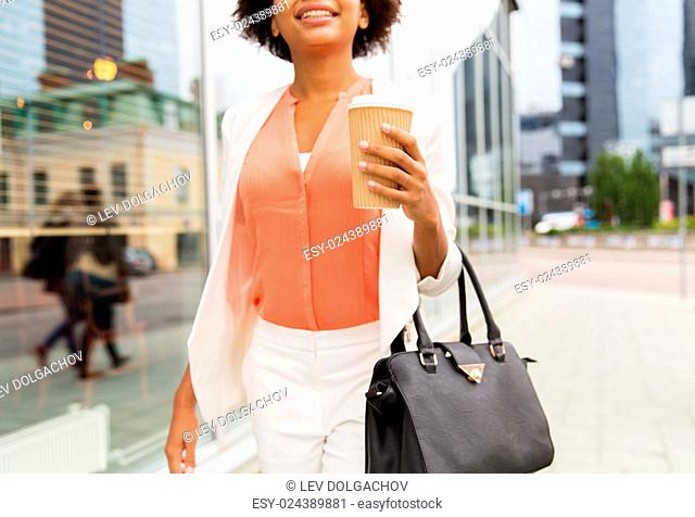 business, drinks, lifestyle and people concept - close up of young smiling african american businesswoman with coffee cup in city