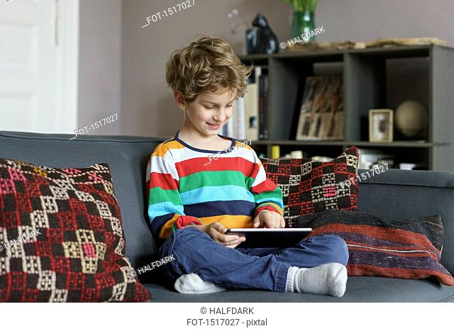 Boy using digital tablet while sitting on sofa at home