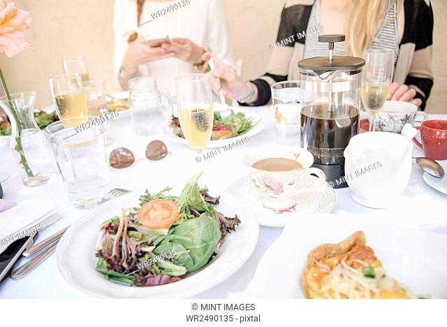 High angle view of a table with food and drink, plates with omelette and salad, coffee and champagne