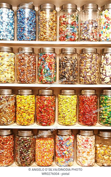 Chocolates kept in different glass jars on selves in shop