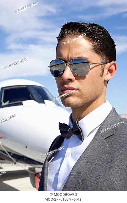 Handsome young men wearing sunglasses with private plane in background