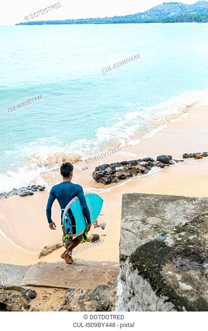Surfer with surfboard on beach, Pagudpud, Ilocos Norte, Philippines