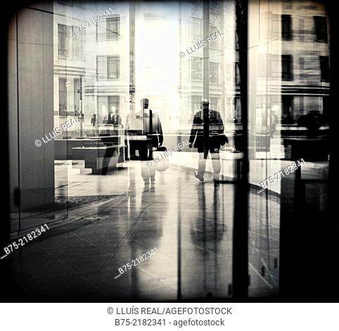 Two unrecognizable businessmen walking down the hall of an office building in the city of London, England, UK, Europe