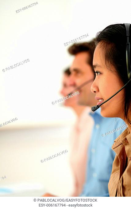 Portrait of young attractive callcenter people using earphone while smiling and sitting on workplace