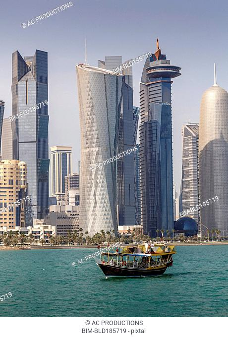 Boat floating near Doha skyline, Doha, Qatar